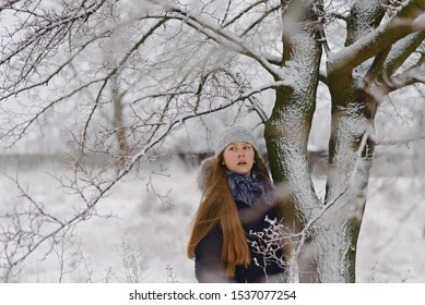 A teenage girl in a knitted hat and a down jacket with long blonde hair stands on a gray winter day near the tree and looks away with her mouth open