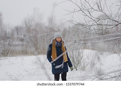 A teenage girl in a knitted hat and a down jacket with long blonde hair stands on a gray winter day, holds her hand in her pocket and looks at the branches of a snowy tree
