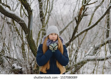 A teenage girl in a knitted hat and a down jacket with long blonde hair stands on a gray winter day against the background of a tree in the forest, hands folded in warm gloves on her chest