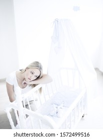 Teenage girl leaning over empty cot