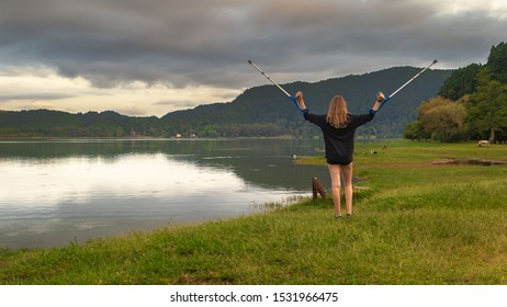 Teenage girl with a leg injury and forearm crutches and winning gesture enjoying the view by a lake and admiring beautiful landscape during sunset