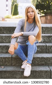 teenage girl with long blond hair and distressed jeans sitting on steps outside - urban lifestyle or street fashion concept