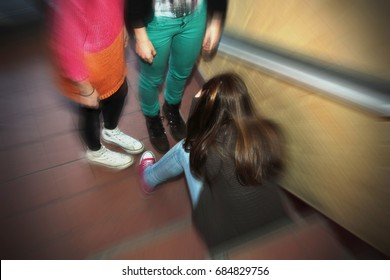 Teenage girl with long, brown hair is sitting on stairs in school, holding her head, two girls stand beside her. Can be used as a concept for headache, migraine, sick, sad or difficulties in school.