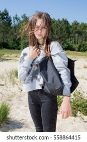 Teenage girl with long hair and her purse walks during the summer holidays