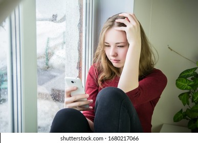 A teenage girl with long hair sits on a windowsill and looks at a cell phone. It is raining outside the window. The concept of dependence on a mobile phone, social networks, isolation, depression.