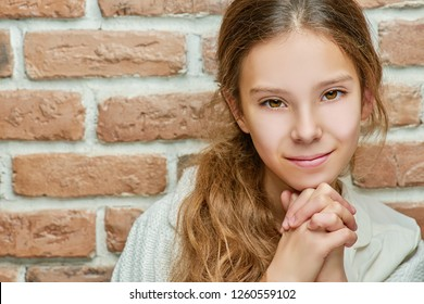 Teenage girl with long hair smiling against brick wall.