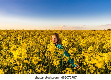 Teenage girl with long hair in yellow bittercress field, sunset time
