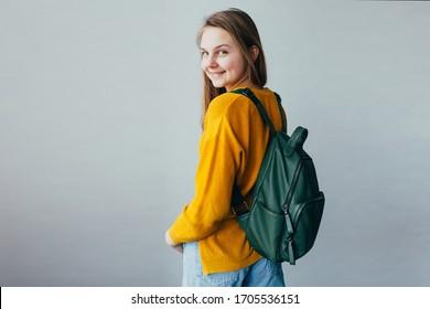 Teenagermädchen, die Kamera anschauen und lächeln. Schönes Studentenmädchen mit gelbem Pullover und blauer Jeans und grünem Rucksack auf Schultern. Trendy Gelegenheitskleidung für Teenager. Hände in Schach