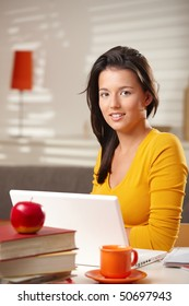 Teenage girl looking at camera smiling sitting at table with laptop computer.