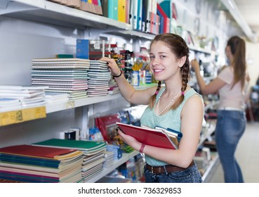 Teenage girl looking different color copybook in stationery shop