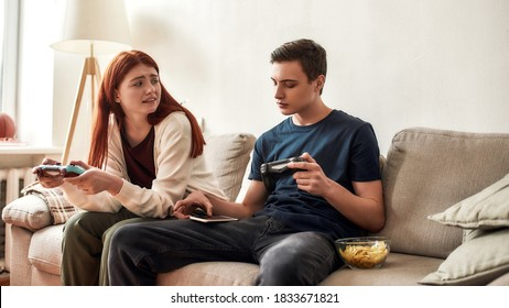 Teenage girl looking irritated at her boyfriend while he got distracted by his phone. Young couple holding game console, playing video games together at home. Technology, smartphone addiction concept