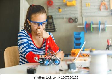 Teenage girl looking at robotic car, school project