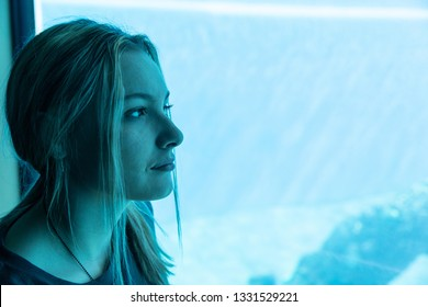 Teenage girl looking through glass at aquarium