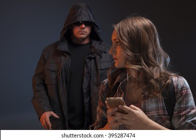 Teenage girl looks over her shoulder because she feels someone is about to attack her. Scary man grabs a girl on her phone.