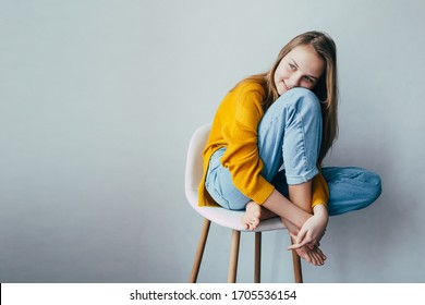 Teenagermädchen sieht Seite an Seite und Sitzen auf weißem, modernem Stuhl mit den Beinen nach oben. Schönes Mädchen in gelbem Pullover und blaue Jeans im Inneren des Hauses. Trendy Casual Outfit. Textstelle
