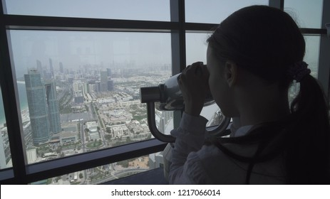 Teenage girl looks through the Abu Dhabi telescope from an observation deck