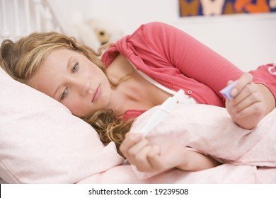 Teenage Girl Lying In Bed Looking At A Pregnancy Test