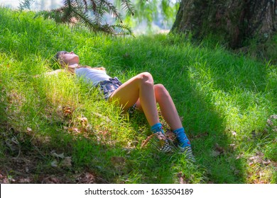 Teenage girl lying in green grass on sloping ground under tree.