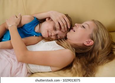 Teenage girl lying on sofa with her younger sister