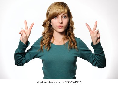 Teenage Girl Making Peace Sign. Thirteen year-old girl making a peace sign with each hand. Note: not isolated.