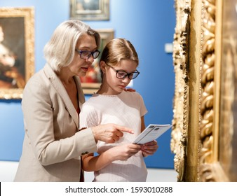 Teenage girl and mature woman observing exhibition in historical museum