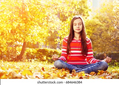 teenage girl meditating in the autumn park on the background of yellow leaves