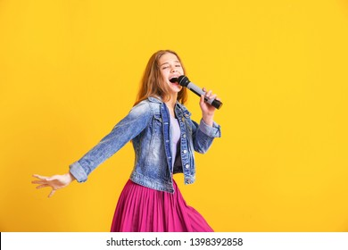 Teenage girl with microphone singing against color background