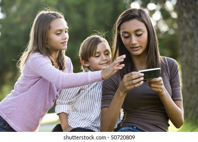 Teenage girl with mobile phone texting while younger siblings watch