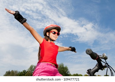 teenage girl on a bicycle with hands up