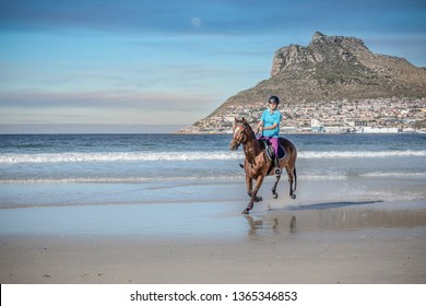 Teenage girl on horseback cantering in the water at low tide on the beach under a cloud sky with a beautiful mountain in the background