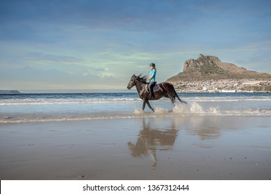 Teenage girl on horseback cantering in the water at low tide on the beach under a cloud sky with a beautiful mountain in the background with a reflection of herself in the water on the shore
