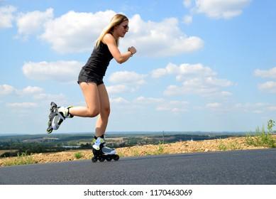 Teenage girl on roller skates at summer. Inline skating on the road.