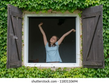 a teenage girl opening the window in the morning