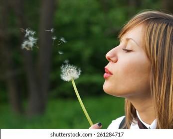 Teenage girl outdoors blowing a dandelion