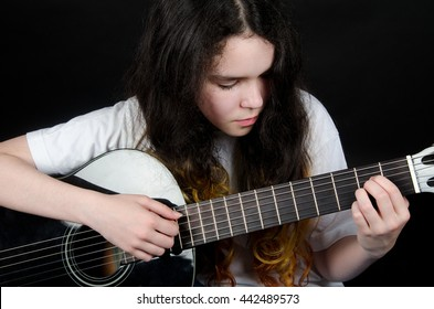 Teenage girl with painted hair playing a black guitar (on a black background)