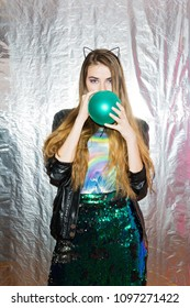 Teenage girl in party outfit posing against silver background blowing a balloon. Studio lighting, silver background, no retouch.