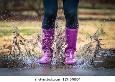 Teenage girl photographed from the waist down wearing black leggings and purple rain boots and splashing in a mud puddle
