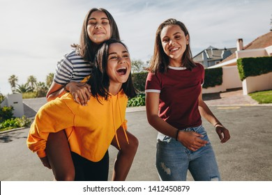 Teenage girl piggy riding on her friend walking in the street on a sunny day. Three smiling girls having fun walking in the street on a sunny day.
