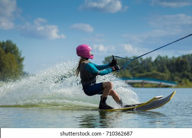 A teenage girl in a pink helmet is riding on the water surface of the lake on water skiing