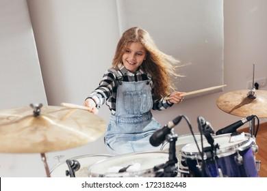 teenage girl playing drums in studio