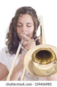 Teenage girl playing the trombone. Isolated on a white background. Studio shot