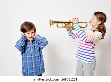 Teenage girl is playing trumpet and her brother is holding his ears