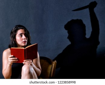 Teenage girl reading a scary book, and behind her a shadow of a man with a knife