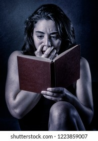 Teenage girl reading a scary book
