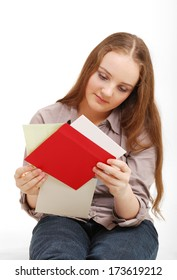 A teenage girl reads cards. She is sitting and holding they in her hands. She is wearing a blouse and jeans.