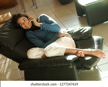 Teenage girl in reclining leather armchair at home using mobile phone