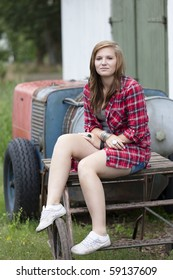 Teenage girl with red shirt sitting down on an old farms table