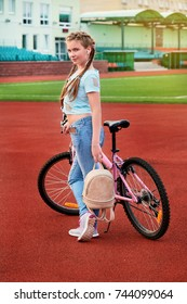 Teenage girl relaxing on a stadium.a child posing with the bike.