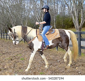 Teenage girl riding a horse in a pasture trying to settle him down so she can take him on trails.