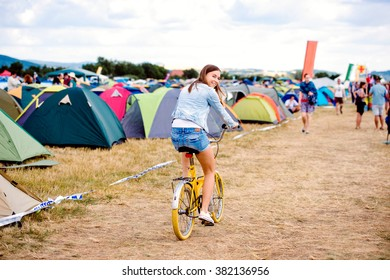 Teenage girl riding yellow bike at summer music festival